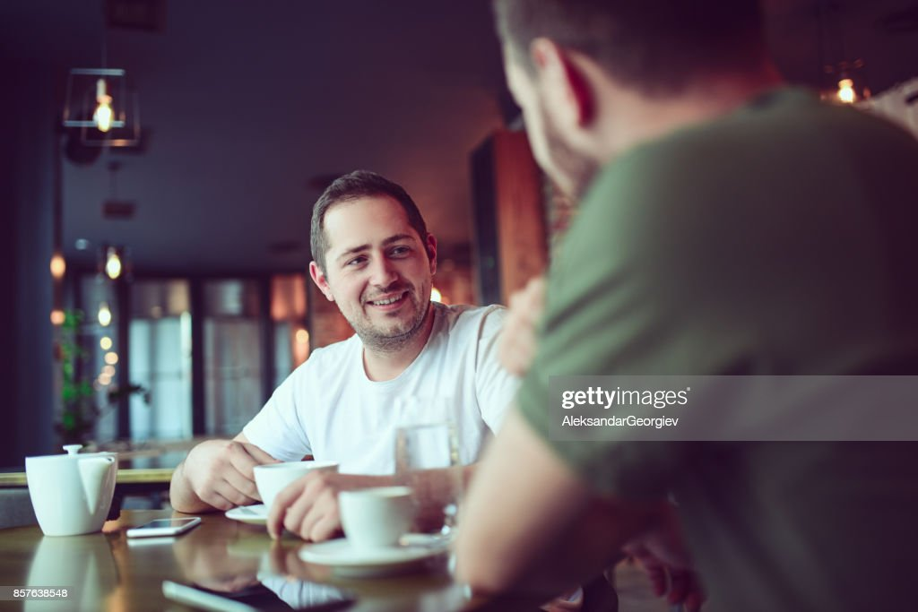 Two Smiling Friends Drinking Coffee and Socialising in a Cafe : Stock Photo