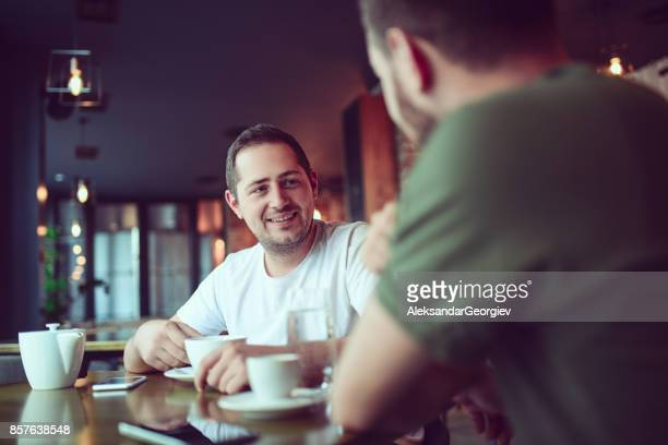 two smiling friends drinking coffee and socialising in a cafe - two people stock pictures, royalty-free photos & images