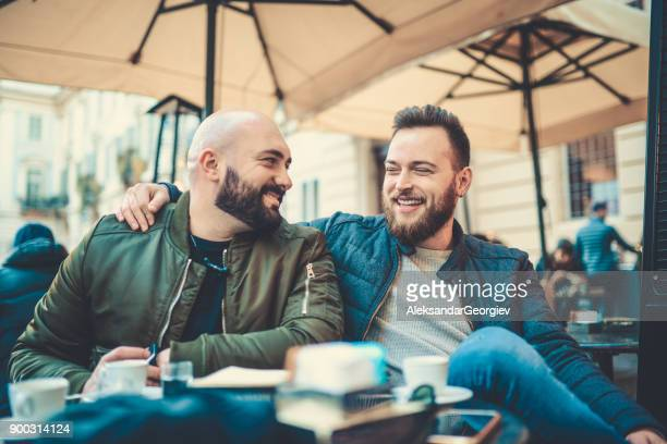 Two Smiling Friends Drinking Coffee and Talking in Coffee Shop