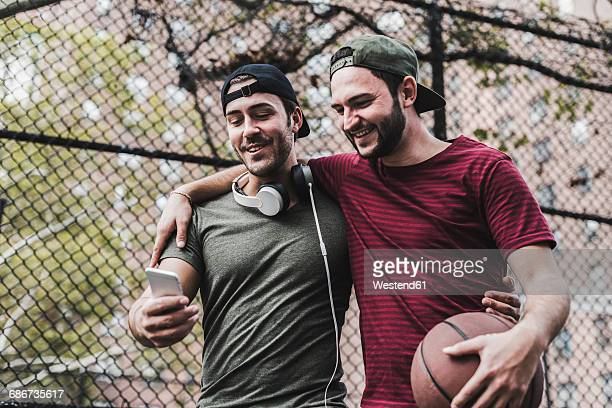 Two smiling friends with basketball and cell phone outdoors