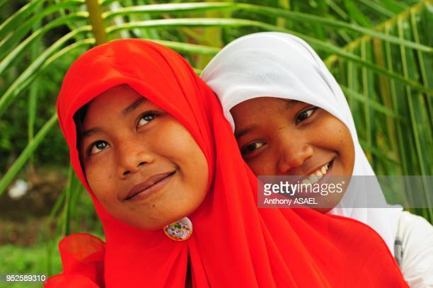 two smiling girl looking up with colorful veil Banda Aceh Sumatra Indonesia