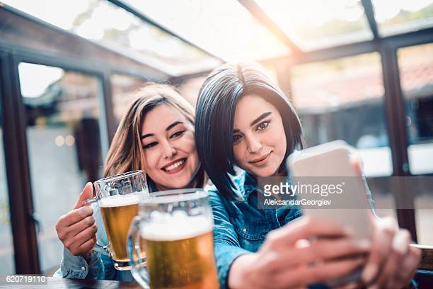 Two Smiling Girls Drink Beer at Bar and Taking Selfie