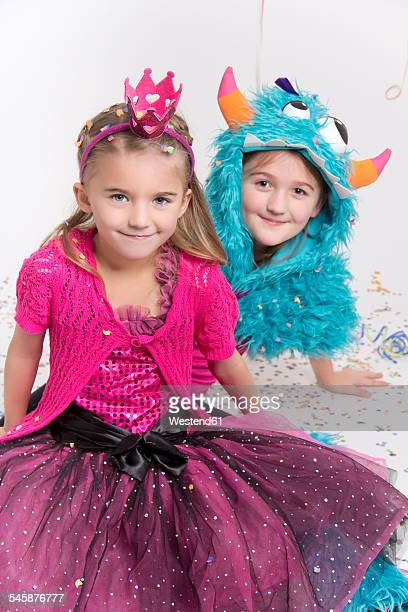 Two smiling girls masquerade as a princess and monster