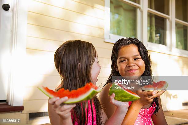 Two smiling girls sitting on house porch with slices of watermelon