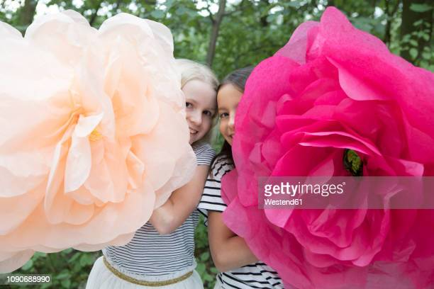 two smiling girls with two oversized artificial flowers - extra groot stockfoto's en -beelden