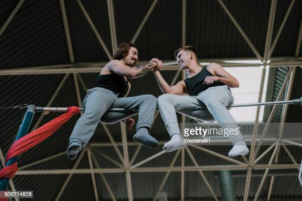 two smiling gymnasts sitting on high bar shaking hands in gym - fair play sport foto e immagini stock