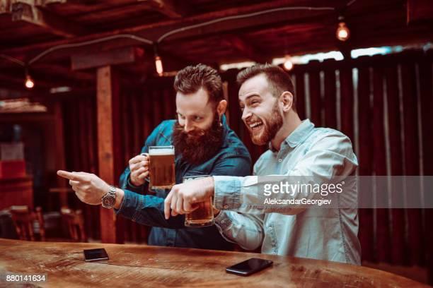 Deux souriant beau amis à la recherche et le pointant sur les filles dans un Bar