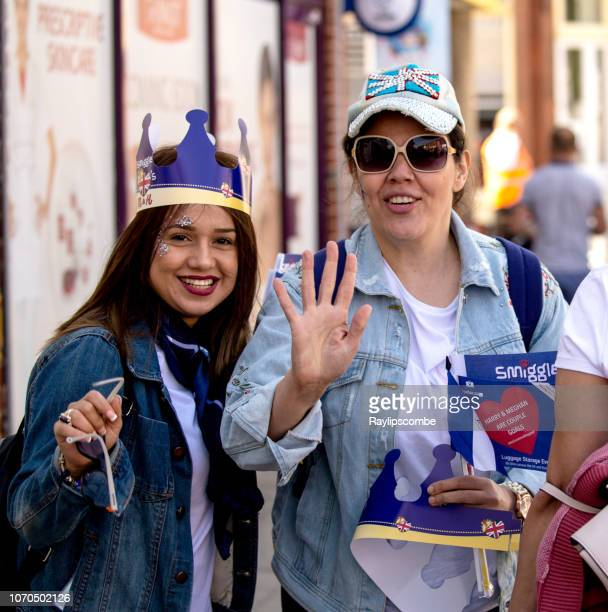 two smiling happy women on their way to celebrate the marriage of meghan markle and prince harry at st george's chapel at windsor castle - meghan stock photos and pictures