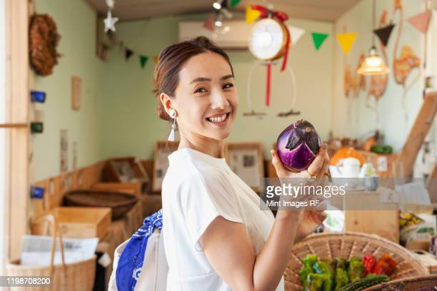 two smiling japanese women standing in a farm shop, holding aubergine, looking at camera. - 30代 ストックフォトと画像