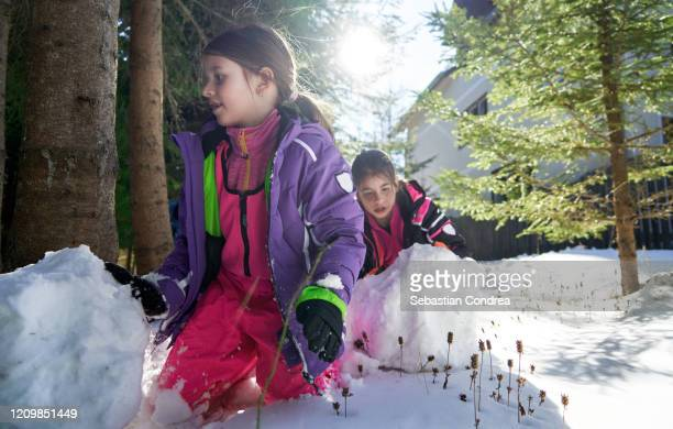 two smiling little girls having fun making snowman, copy space, playing with sonw in mountain baisoara, romania. - 2 5 months stock pictures, royalty-free photos & images