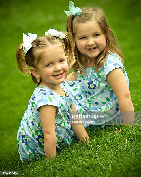 Two smiling little girls in blue dresses on hill