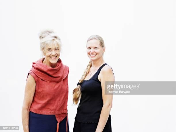 two smiling mature women against white background - side by side stock pictures, royalty-free photos & images