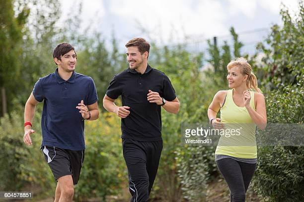 Two smiling men and woman jogging