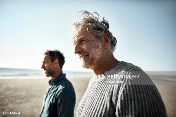 two smiling men on the beach - son stock pictures, royalty-free photos & images