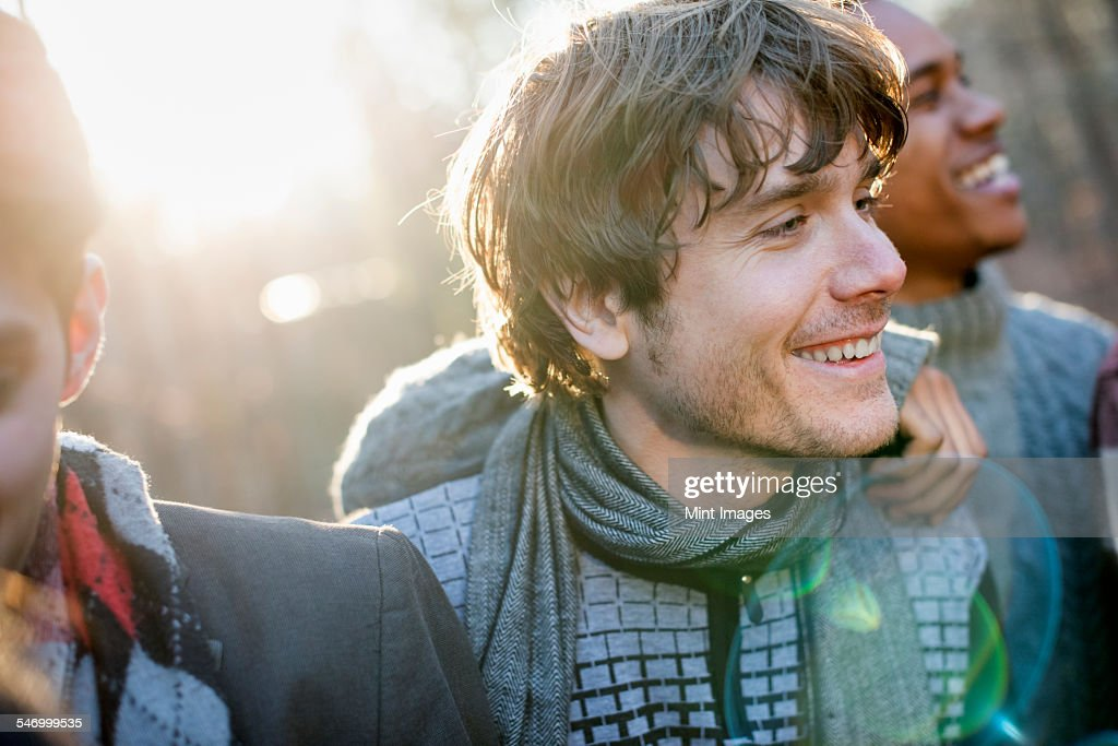 Two smiling men standing in a sunlit forest in autumn. : Stock Photo