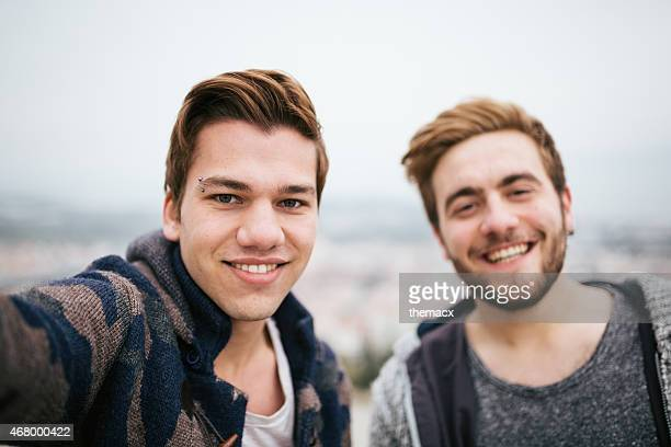 Two smiling men taking selfie with blue background