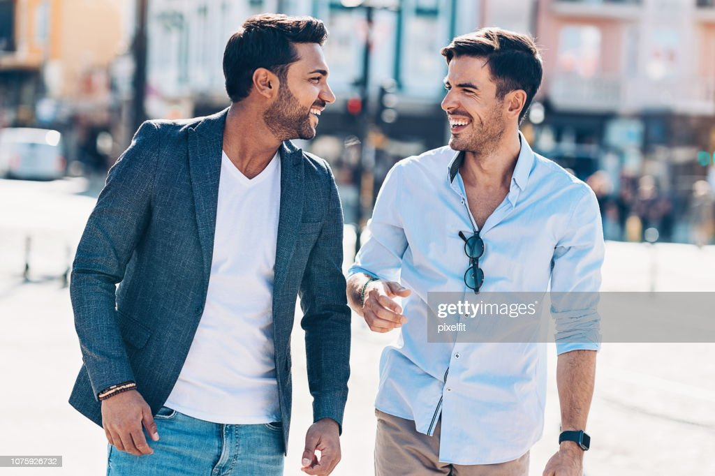 Two smiling men walking together and talking : Stock Photo