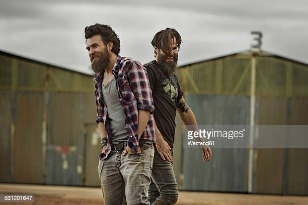 Two smiling men with full beards in abandoned landscape