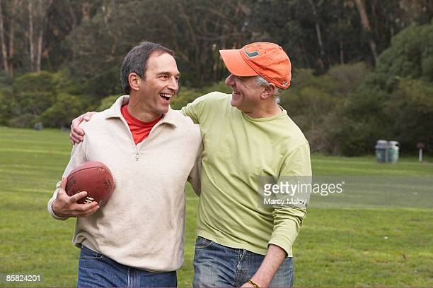 Two smiling middle-aged men in the park.