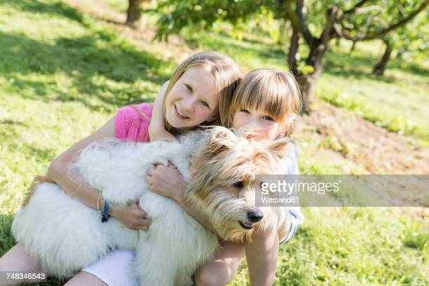 two smiling sisters cuddling with dog on meadow - hundeartige stock-fotos und bilder