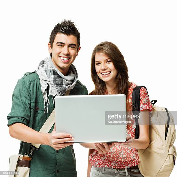 Two smiling teenagers with laptop