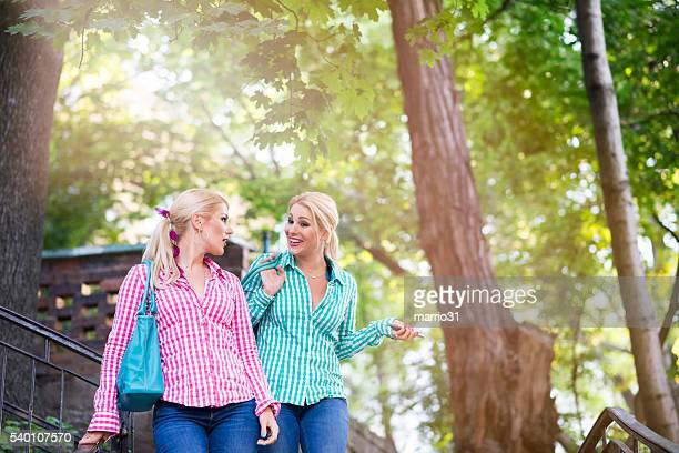Two smiling twin sisters walking in the park