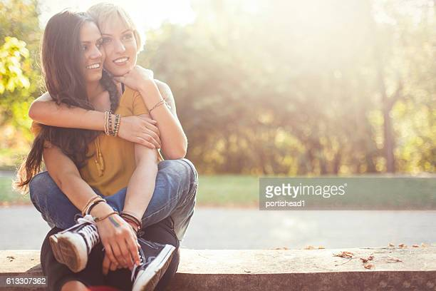 Two smiling woman sitting and embracing