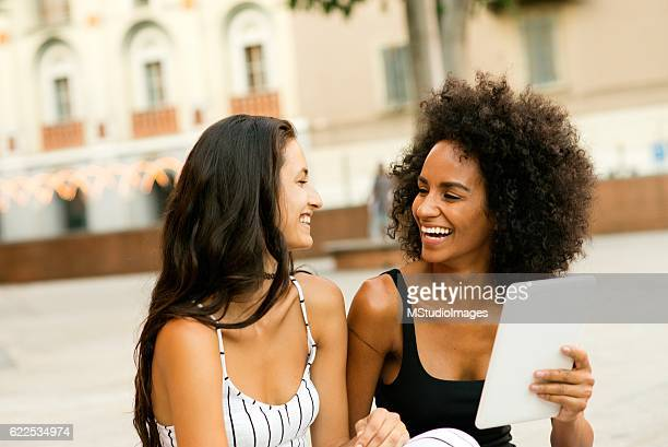 Two smiling woman using digital tablet.
