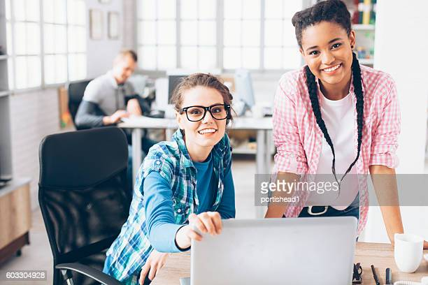 Two smiling women at workplace