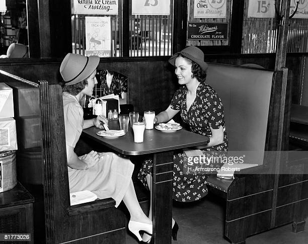 Two Smiling Women Both Wearing Hats 1 Wearing Dark Print Dress Sitting In A Booth Having Sandwiches & A Glass Of Milk Pumps Signs Water Condiments.