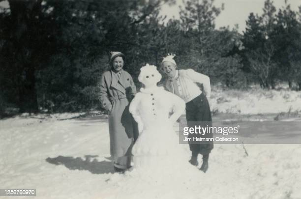 Two smiling women in winter clothes pose alongside with a lifesized snowwoman they have created circa 1939