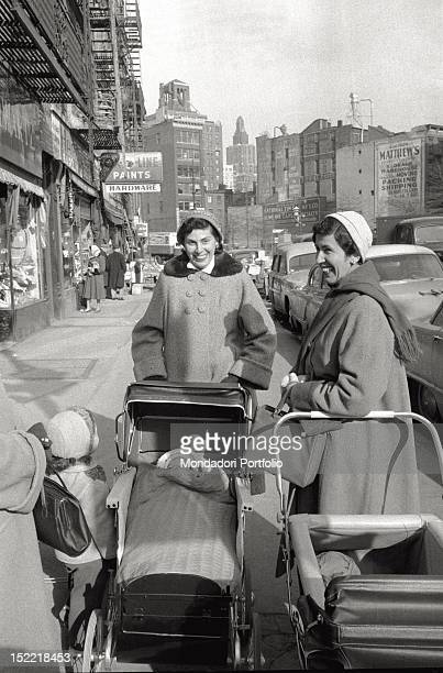 Two smiling women meet up in the street in a popular background they have prams and in one of them can be seen a baby while another child looks at...