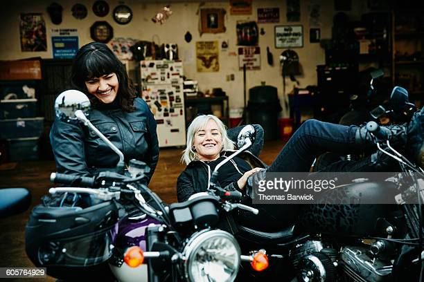 Two smiling women relaxing on motorcycles