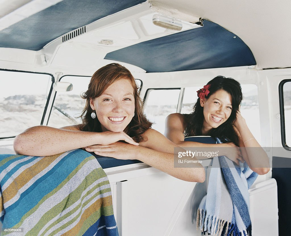 Two Smiling Women Sitting in a Camping Van : Stock Photo