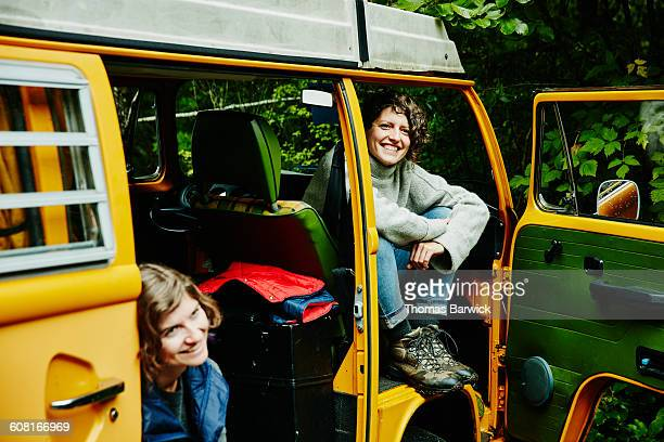 two smiling women sitting in van after hike - leanincollection stock pictures, royalty-free photos & images