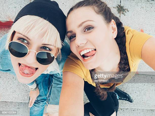 two smiling women sitting on colorful stairs and having fun - ados lesbiennes en couple photos et images de collection