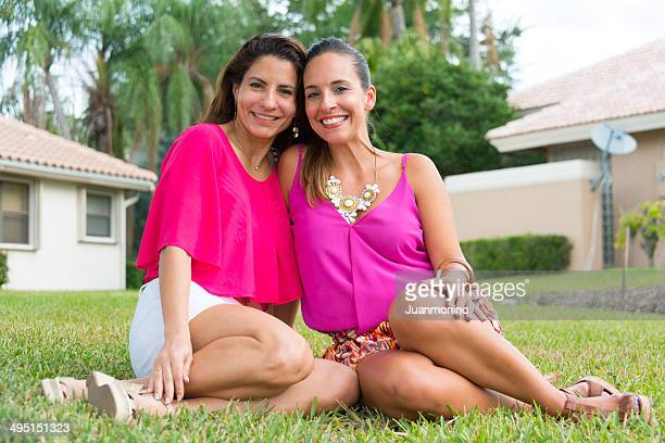 Two smiling women sitting on grass outside residence.