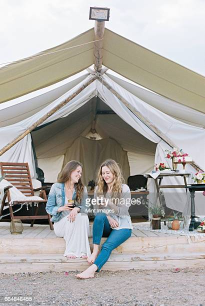 Two smiling women sitting outside a large tent laughing and having a glass of wine.