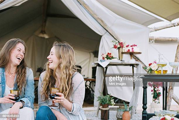 Two smiling women sitting outside a tent in a desert, enjoying a glass of wine.