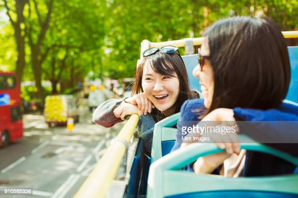 two smiling women with black hair sitting on the top of an open double-decker bus driving along tree-lined urban road. - double decker bus stock pictures, royalty-free photos & images