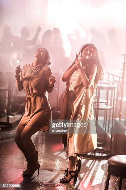 Two smiling women with champagne glasses dancing in a club.