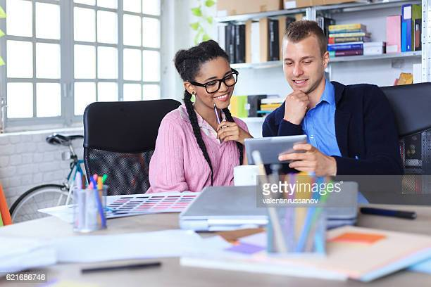 Two smiling young coworkers using digital tablet in the office