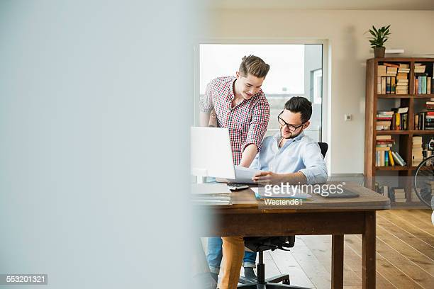 Two smiling young men at desk with documents