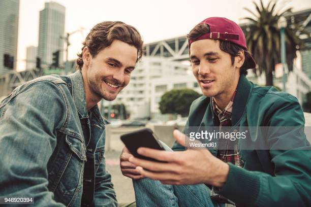 two smiling young men sharing cell phone outdoors - varón fotografías e imágenes de stock