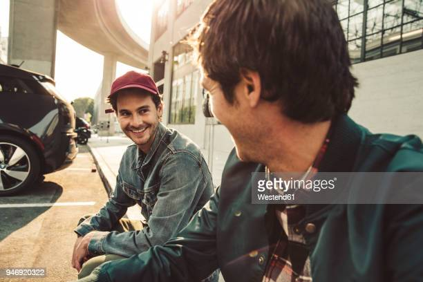 two smiling young men sitting on sidewalk - only men stock-fotos und bilder