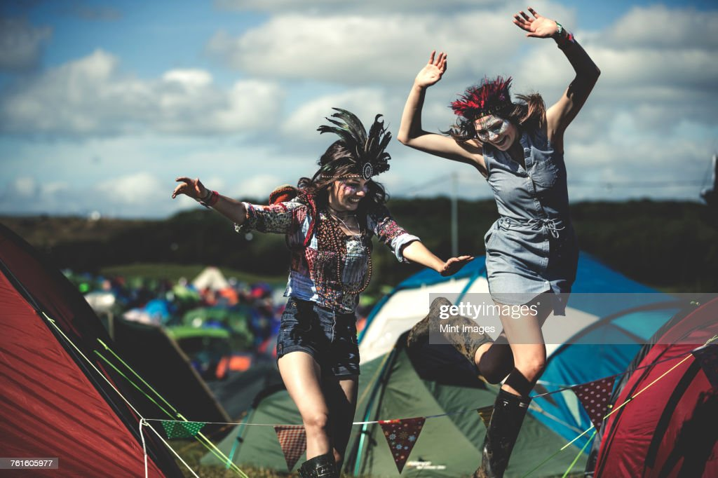 Two smiling young women at a summer music festival face painted, wearing feather headdress, jumping among tents. : Stock Photo