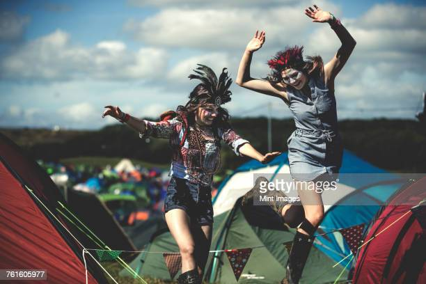 Two smiling young women at a summer music festival face painted, wearing feather headdress, jumping among tents.