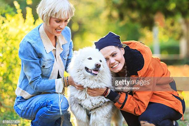 Two smiling young women caressing a samoyed dog
