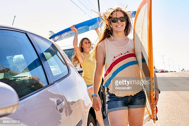 Two smiling young women carrying surfboards on coastal road