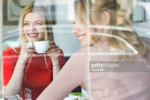 Two smiling young women in a cafe